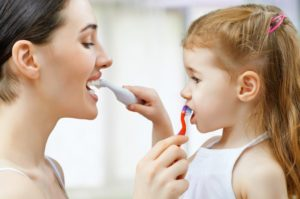 A mother and daughter brush each other's teeth.